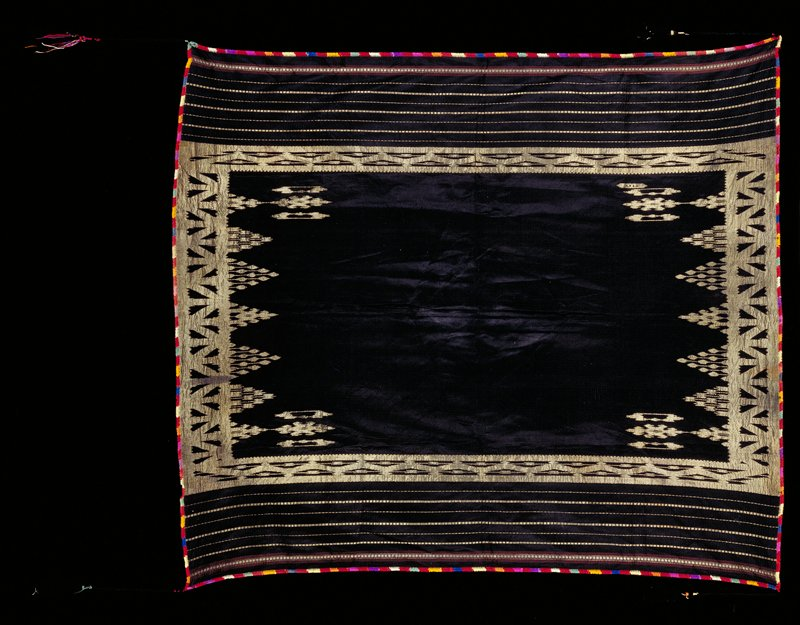 Black with geometric designs on edges in gold metallic thread; gold stripes on long sides with red and gold stripes at edge; trimmed in multicolored embroidery; tassel attached to long black cord at each corner
