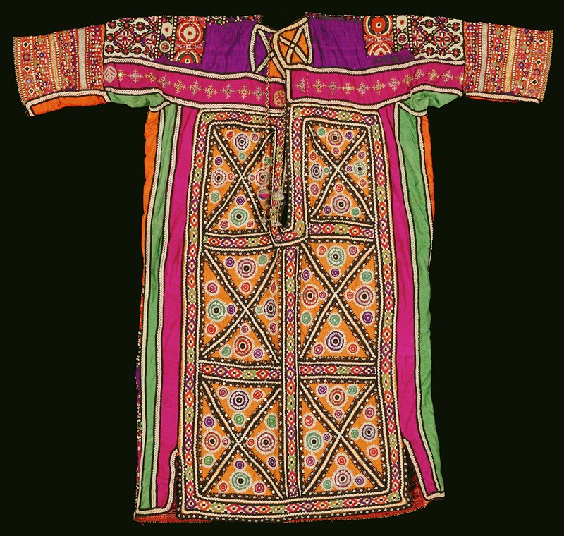 Shirt with long neck opening with multicolored braided tassels trimmed with bells; allover multicolored embroidery in geometric designs (mainly circles); multicolored sequins and shiny metal disks encorporated throughout design SO / EMB