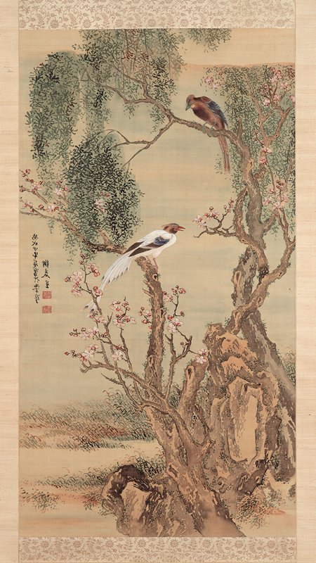 crested white bird and crested brown bird perched on the branches of a gnarled, twisting tree with pink blossoms; blossoming tree is intertwined with a willow tree, with a rock between the two tree trunks; low grasses on ground