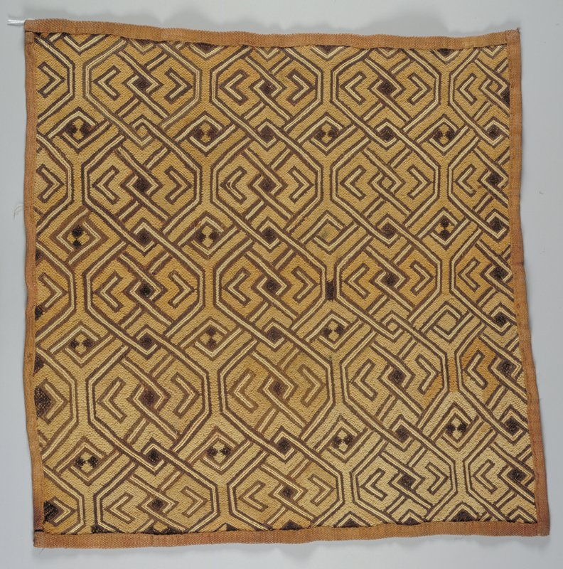 Geometric design of interlocking 6-sided figures with other lines between; shades of tan and brown. Surface ornamentation (Needlework)