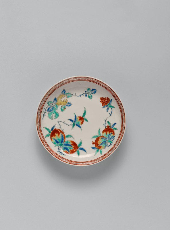 small dish with colorful fruits including peaches, pomegranates, and citron; red, green, blue, and yellow; geometric zigzag pattern around inner lip