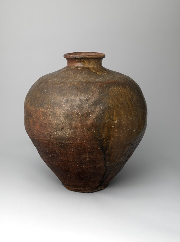 large, brown ceramic jar with short, reddish-brown neck and lip; area of dripping, dark glaze down one side+