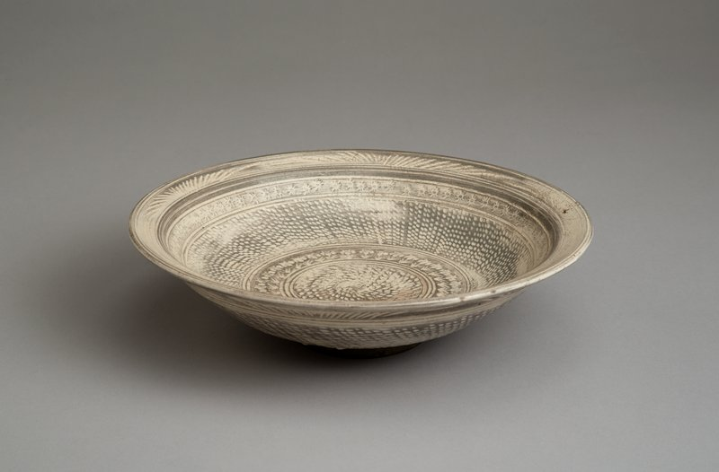 plate with shallow, upturned edges on small foot; decorated with bands of diagonal spots, floral motifs, and starbursts inside in white and gray colors; large band of spots on outside with reed-like motif around mouth