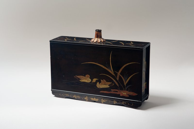 rectangular sake container with two gold ducks swimming away from a sprig of reeds on either side; small, graceful willow with lotus leaves on shore on both short ends; grass design on top with spout top center