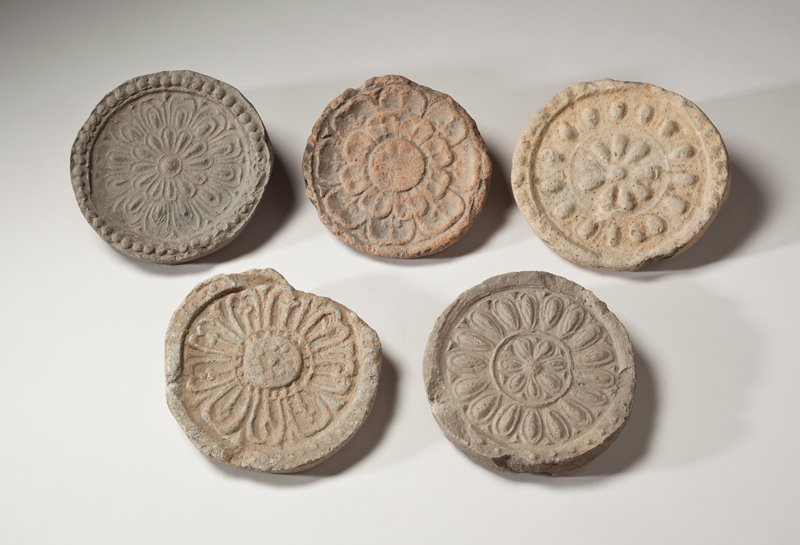 round roof tile end with pinkish cast; impressed lotus design with wide petals and wide, round center