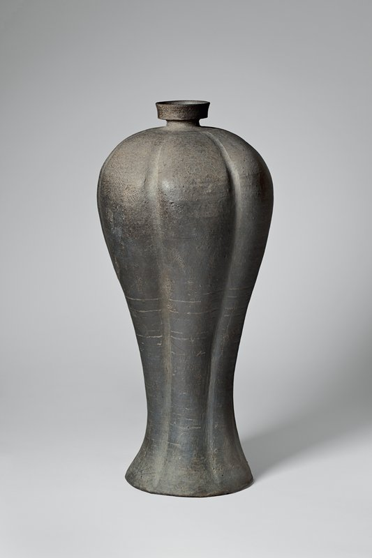 tall vessel with graceful widening near top; fluted into six sections; short, thin neck with high mouth; two concentric inscribed circles below neck; horizontal inscribed markings around center