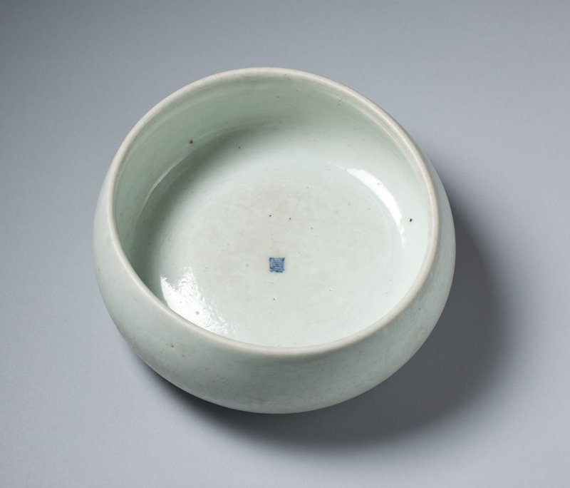 low sided white bowl; thick walled with sunken foot; cobalt seal with character in center inside; whitish glaze with bluish tint