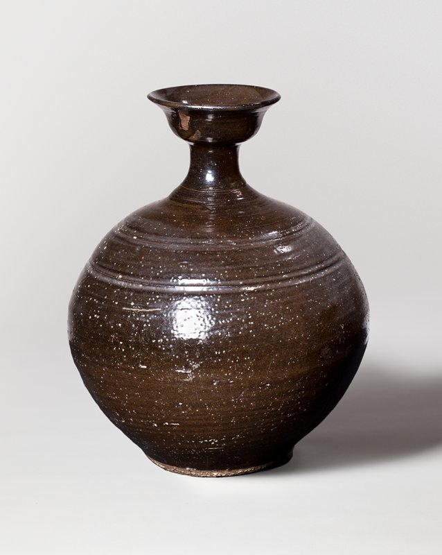 jar with rounded body, very narrow neck, and wide, flared mouth; thin incised bands around neck and shoulder; dark brown glaze