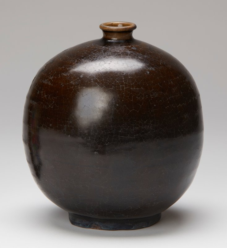 round vase with oval shape; very short neck, rolled lip; dark brown glaze with darker brown and hints of navy blue coloring near bottom; horizontal dark line near bottom of body