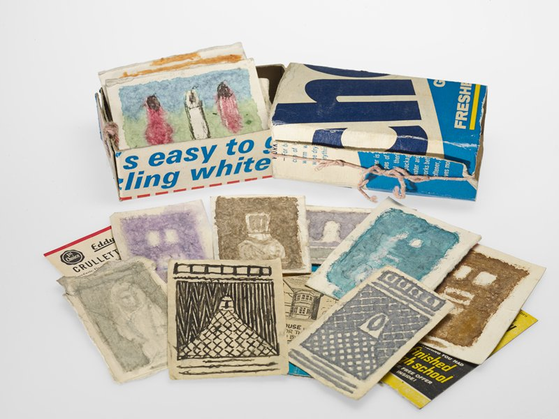 matchbox-style cardboard box made from a Cheer detergent box with printing primarily in blues and yellow; pink string holds side of cover closed and holds ends of box closed; box contains various ephemera--including matchbook covers, small bits of newspaper with images, portions of cardboard and paper consumer product packaging--and mainly figurative drawings--some on rough paper, some on bits of packaging/cardboard