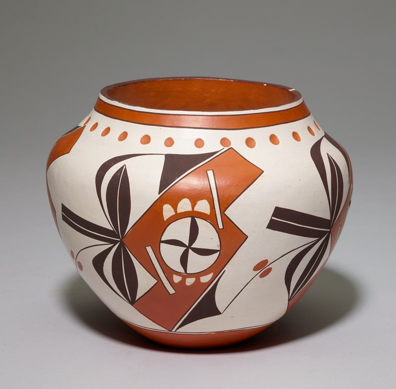 white ground with terra cotta and dark drown detail; wide shoulder with short vertical neck and wide mouth; small foot; terracotta band around neck with dots below central pattern is geometric in terra cotta color and stylized vegetal forms in dark brown