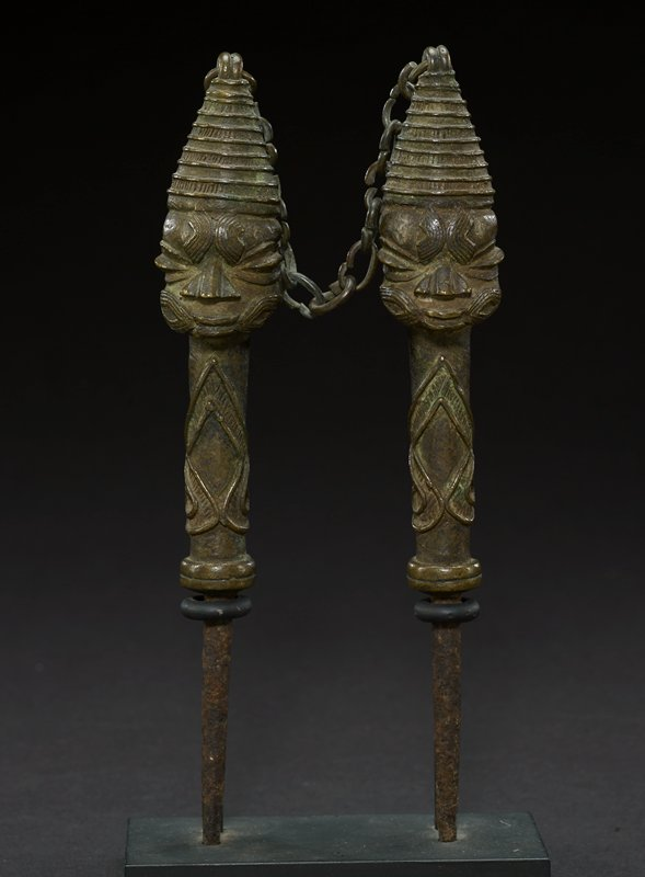 one of two figurative brass staves, which are attached by a chain at the tops of their cone-shaped headdresses; this figure has been identified as male (the other female); however, the staves appear identical, with wide, oval eyes, wide pointed noses, and a small mouth with slightly parted lips; both figures have patterned decoration on their forehead and cheeks; both wear a beehive shaped headdress that ends in a point; the heads are attached to the body of the stave, which has an ornate design; main body of stave is cylindrical in shape, below it the stave leads into a point; staves are all one brass color, with the bottom section appearing to be a more brownish color