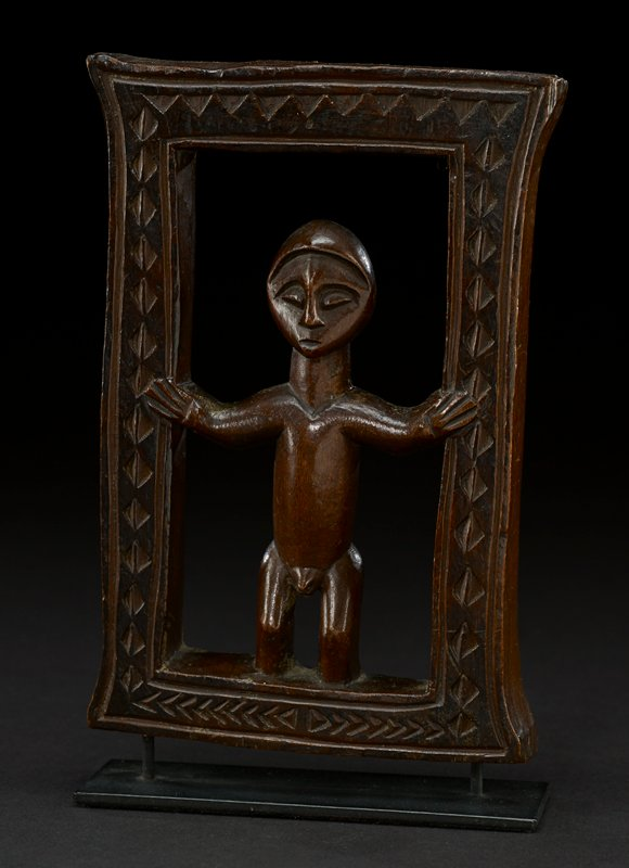 wooden figure stands with arms outstretched and legs slightly bent inside a rectangular frame with minimal decoration; figure has round head, with a simple, smooth headdress; his eyes are oval, his nose angular, and his triangle-shaped mouth small and slightly open; figure's neck is long and wide, his torso is a round cylinder, and his genitalia are exposed; the figure is footless--his legs disappear into the frame; the entire piece is a dark reddish brown, the natural hue of the wood