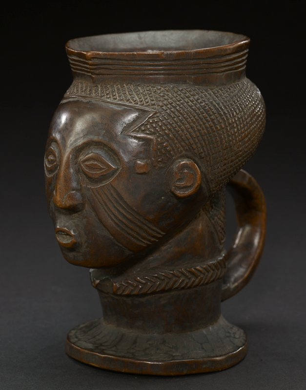 cup is carved into likeness of a head that leads down to a pointed chin; lip of the cup has hard edge that is raised from the head and carved in flowing lines; face has large, oval eyes, a small, round nose, and an O-shaped mouth; multiple curved lines run down from the bottom of the eyes to the jawline; there is a small circle carved in space between eye and ear on both sides of head; the hair is intricately carved in a grid pattern with a braided, rope-like pattern at back; neck attaches to round, flat base of cup and is adorned with a carved necklace (?); curved handle runs from base of head to base of neck; the entire piece is the dark-brown hue of the wood from which it is carved
