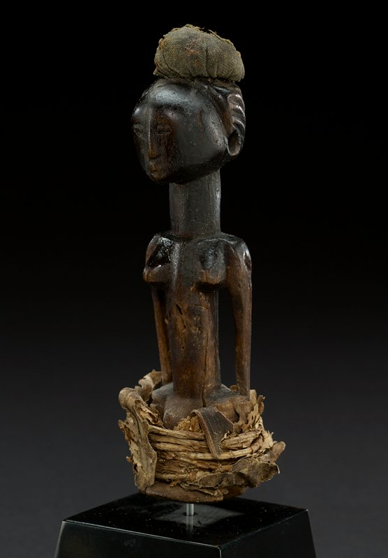 figure wears a small rounded cloth and fiber headdress perched on the top of the head; head is round and smooth with carved hair extending to the back of the head; face has small, carved eyes, a small raised nose and a small carved mouth; figure has a long thick neck; chest has prominent breasts; arms are thin, long and fall straight from the shoulder; abdomen is tall and long and ends in a fiber base; dark wood