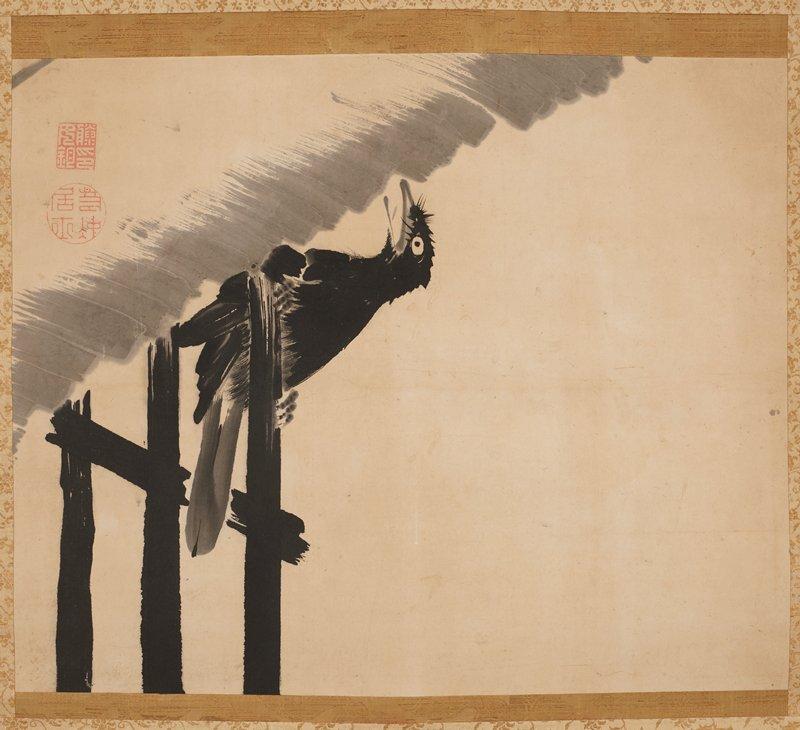 black bird grasps onto partial black fence and cranes neck upward, beak open, with a gray cloud overhead