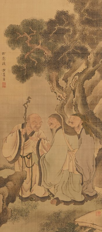three men, one with a knotty cane, stand under a tree near a rock conversing and gesturing
