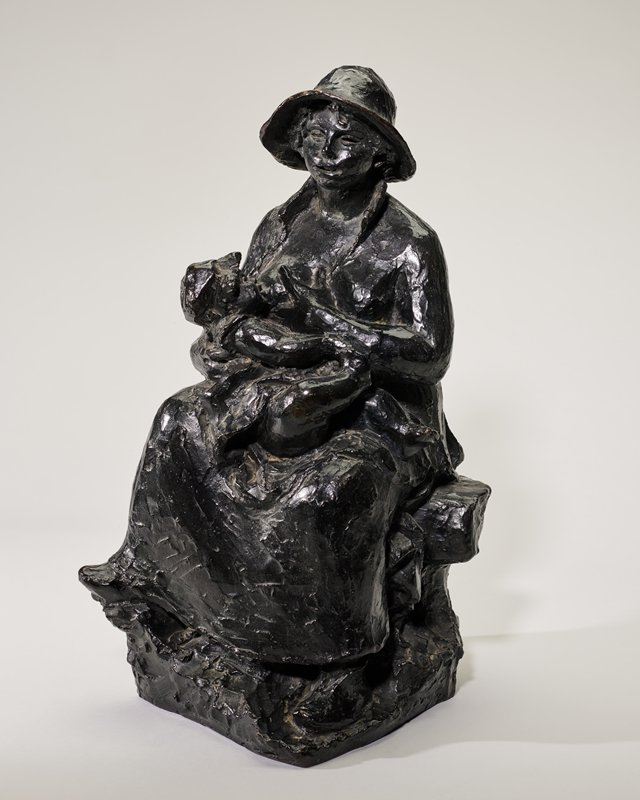 heavy-set, seated young mother with her hair in a braid down her back, wearing a brimmed cap and an open coat, nursing a baby girl wearing a dress and a bonnet; dark patina