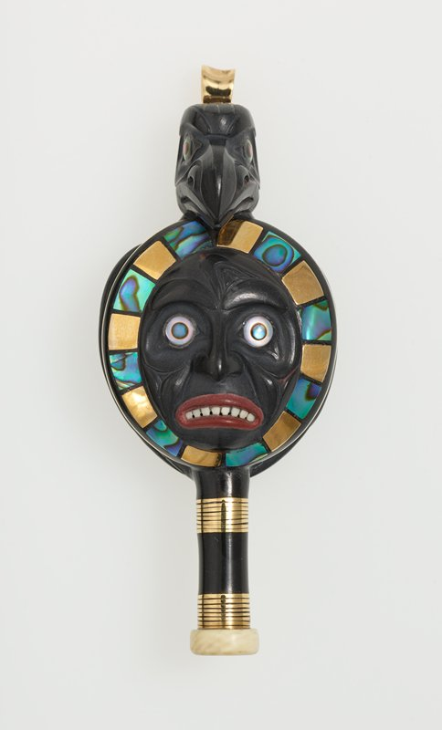primarily black; maskette with round eyes and frowning mouth with red lips and visible white teeth; alternating gold and mother-of-pearl inlays around face; raptor's head at top with wings on back, with rust red inlays on top of wings and mother-of-pearl at center of back; vertical element wrapped with gold wire and tipped in ivory at bottom