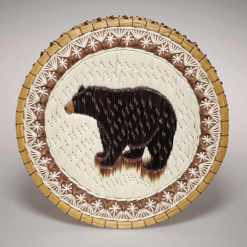drum shaped basket with flat cover and bottom; birch bark base with quillwork on exterior; cover has white ground with image of a black bear and a border of white stars and brown and white X-shapes; similar stars and X-shapes in two bands on body of basket
