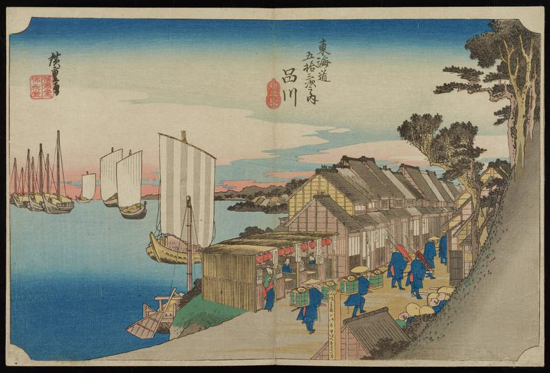 storefronts lining a road on shoreline with large boats; procession of travelers in blue walking along road; gray hill at R with trees
