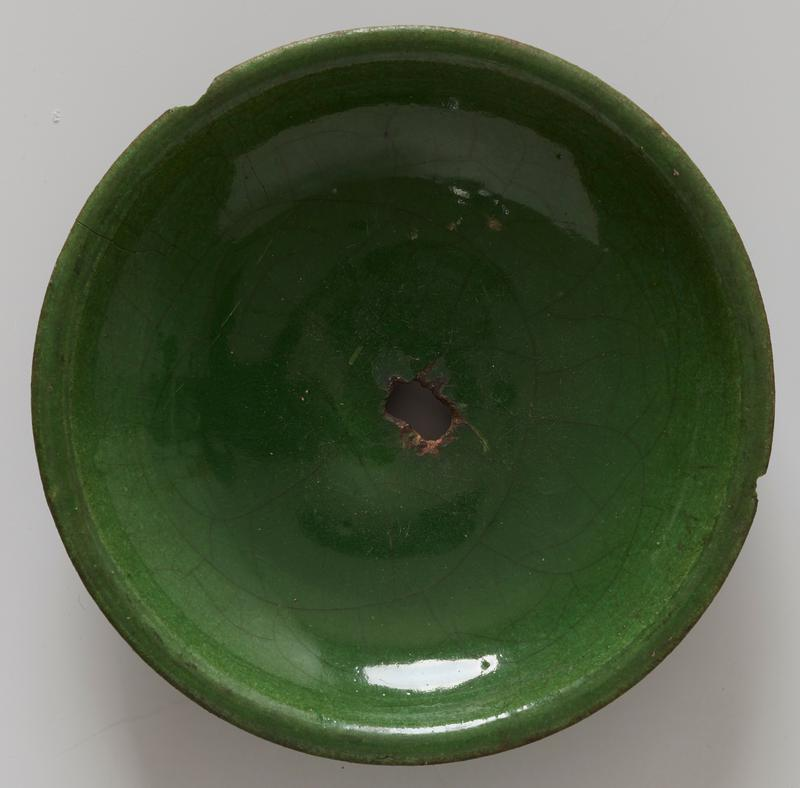 low dish coarse buff paste; green glaze inside, coarsely crackled; outside similar glaze flowing toward contracted foot; hole broken in center.