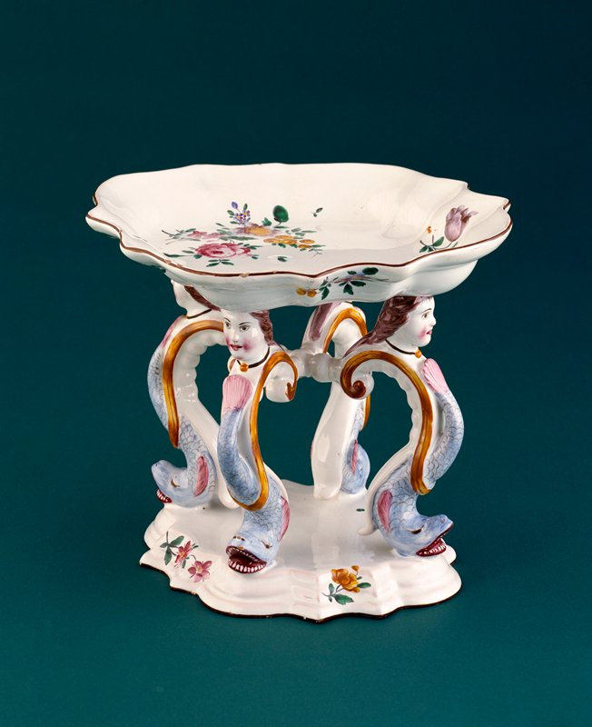 oval-shaped shallow bowl painted with a central tied-flower spray within a border of foliage scrolls and flowers suspending drapery; supported on four dolphin and female mask legs resting on an oval-shaped stepped base with stylized flowers and foliage