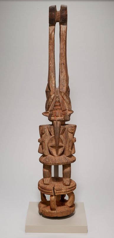 standing stylized figure with pointed beard; triangular-shaped ears; pair of very tall horns with spirals at top; face has deeply-incised geometric patterns--without facial features; deeply carved oval element with horizontal band on chest; figure wears short skirt-like garment; figure stands on round platform with four curving legs and one vertical central leg; some possible scattered bits of red and white pigments