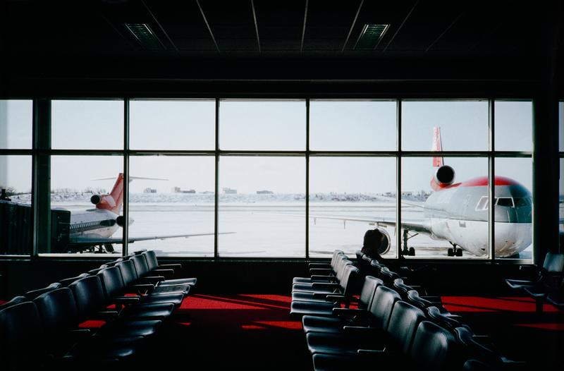 airport gate waiting area with a large bank of windows overlooking bleak winter runway; red and gray Northwest airplane parked on either end of the window; rows of vinyl seats on red carpeting aligned perpendicularly to window with lone figure at R
