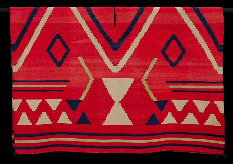 red background with large tan and navy diamond pattern across C (over shoulder area); stepped pyramid pattern in tan and navy along lower edges; navy and lime colored stripes along borders