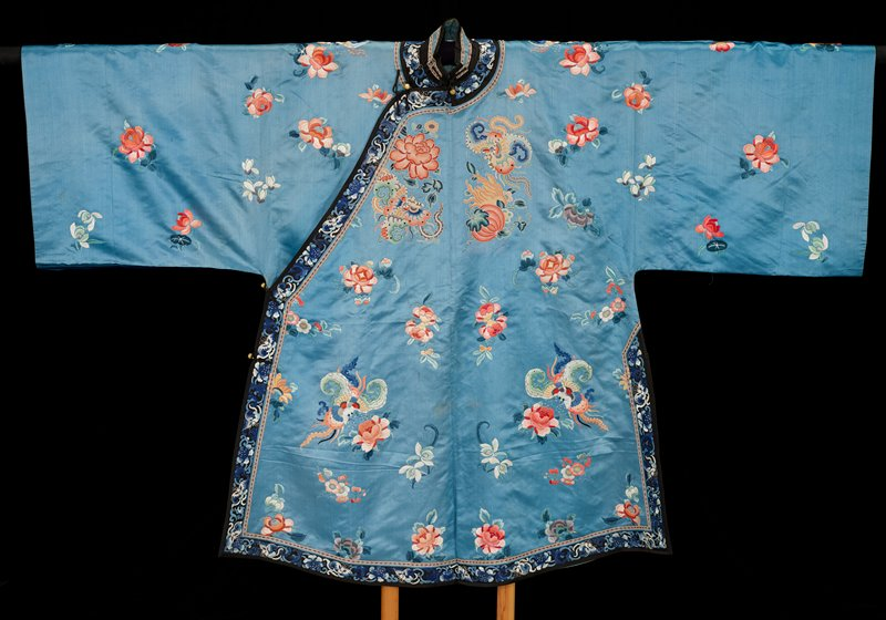 medium blue; embroidered overall with primarily salmon-colored flowers and moths/butterflies; black trim embroidered in white and shades of blue with flowers and butterflies; blue lining; inside of cuffs are salmon-colored silk embroidered with similar flowers and insects and trimmed with ribbon