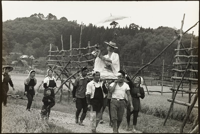 seated man with a goatee wearing a light-colored kimono and a straw hat and holding a bundle of sticks and a metal teapot being carried on a litter by group of young men; woman at right holding an umbrella tied to a long stick over man's head; three woman and a child walk behind litter in a procession through countryside, with wooden trellis-like structures behind figures on path; trees in background