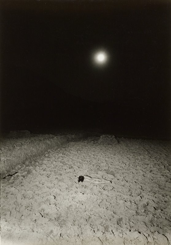 nude figure with long dark hair lying face down in a plowed field; black sky with bright, out of focus moon