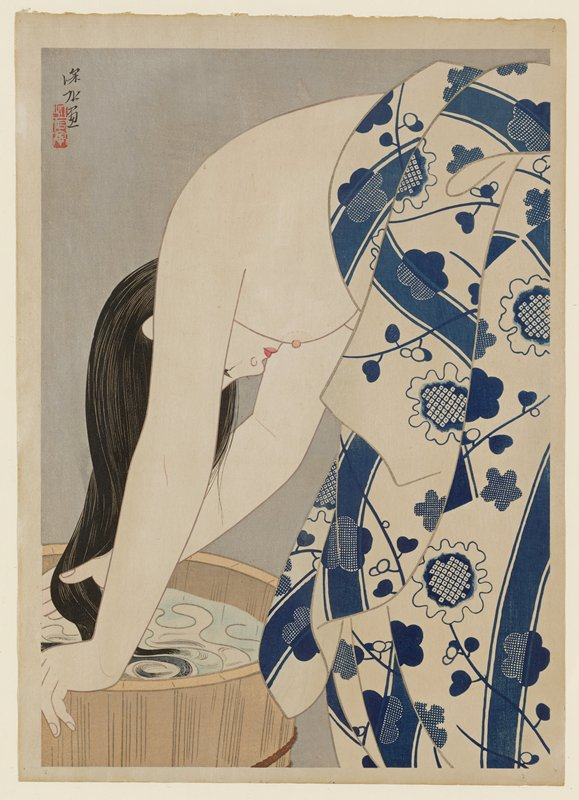 image of woman with long dark hair bending forward; top of woman exposed with a blue and white flower patterned towel covering bottom half; washing hair in a barrel filled with water; gray non-descript background