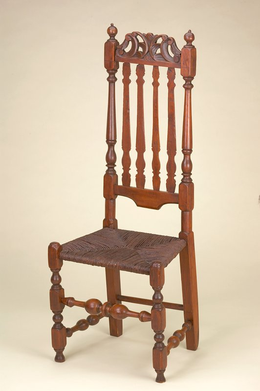 side chair with high back; scroll and foliage carved element at top of back; 4 split turned spindles (decorated side toward rear) between carved and turned spindles on seat back; seat of woven cane; large bulbous elements on turned horizontal leg supports