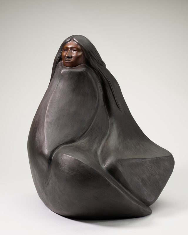 woman seated cross-legged with her body completely covered with a brown blanket, with only her face and long loose hair visible; woman looks over her PR shoulder; bronze-colored face