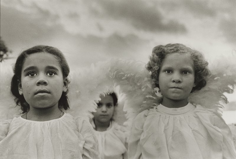 black and white photograph of three young girls in white, wearing feather angel wings; girl at L is looking up, girl at R looks directly at camera; girl in background, out of focus, looks upward