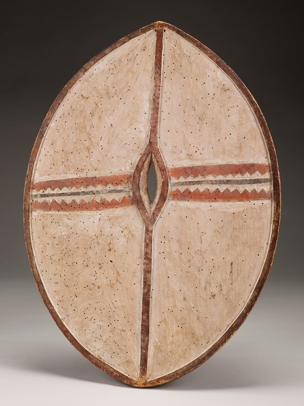 two-sided wooden shield; one side has concentric linear pattern with brown and red alternating triangular shapes lining sections alternating a negative space of white pigment; tiny hole in center with a wooden arm shield at one end; the other side has mostly white pigment with two rows of lines with triangle patterns on one end in red pigment; thin dark line in between triangle rows; thin red line intersects with triangle lines, outlining a center hole; dark wooden border around outer perimeter