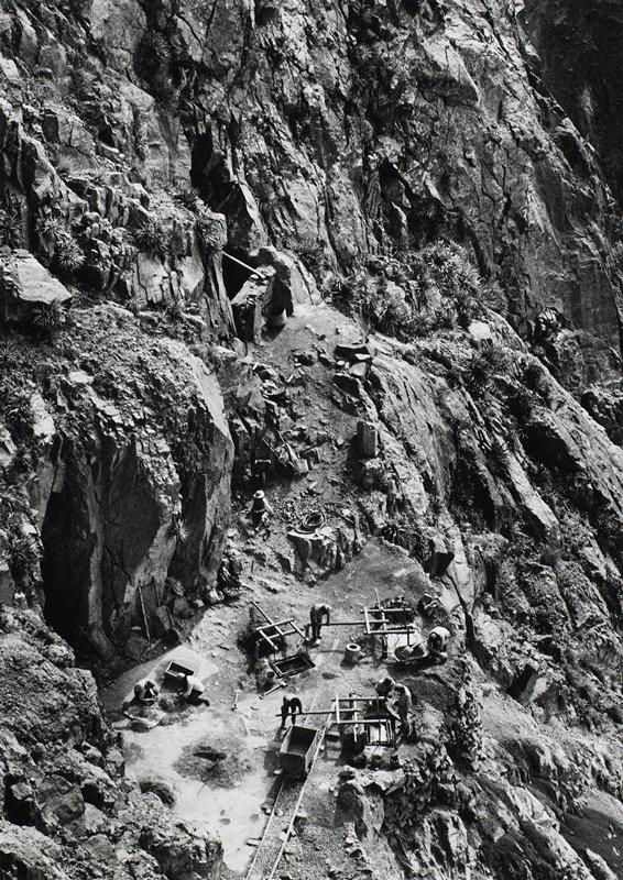 overhead view of miners working on the side of a mountain; 2 caves visible