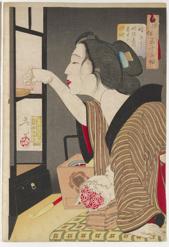 woman leaning forward, with her brown and yellow striped kimono with black collar slipping off her PL shoulder, lighting a small lamp on a black lacquer shelf, with a pillow roll beneath her; tan basket or box with black handle and red and yellow object (pipe?) between woman and shelf