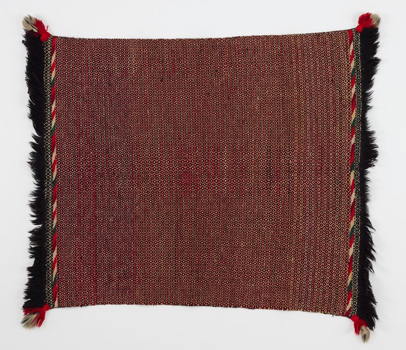 small, tightly woven textile with tiny, alternating black, red, and white diamond pattern with spots; black fringe along short ends; black and white diamond border under border of diagonal green, white, red, and cranberry stripes
