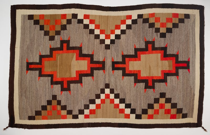 brown and cream borders; grey ground with two stepped diamonds with brown centers and orange and dark brown borders, with orange triangles at corners; stepped squares in light brown, dark brown, cream and orange at long sides; two corners have twisted brown tassels