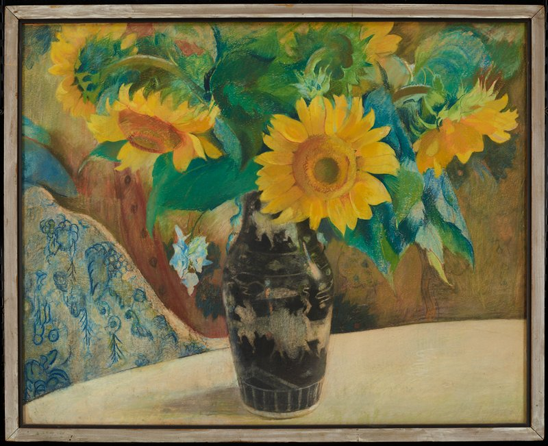 bouquet of sunflowers in black vase with white decorations; on white tabletop; blurred brownish background; upholstery at L with blue designs and grapes
