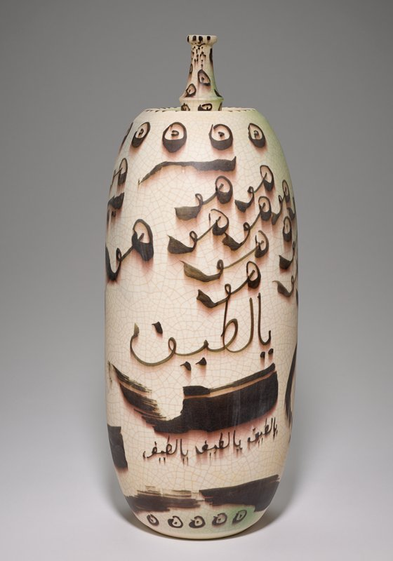 cream colored ceramic vase with pale green shading at the top and bottom; faux crackling throughout; brown dimensional script throughout; oblong in shape with a thin neck and small opening