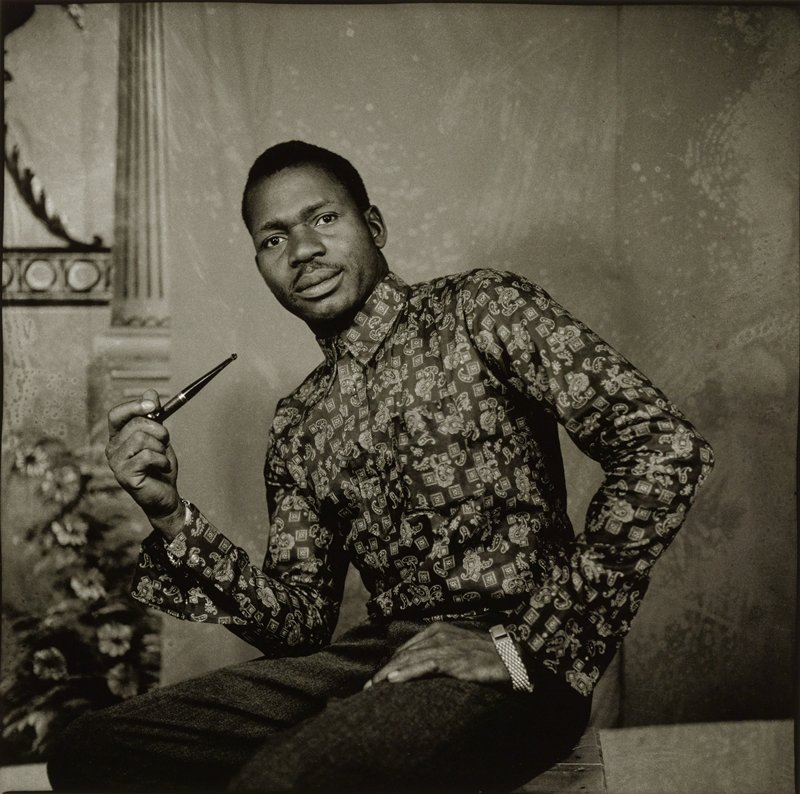 portrait of a black man wearing a paisley patterned long-sleeved shirt, with his PR elbow on his PR thigh and his PL hand on his PL thigh, holding a pipe in his PR hand