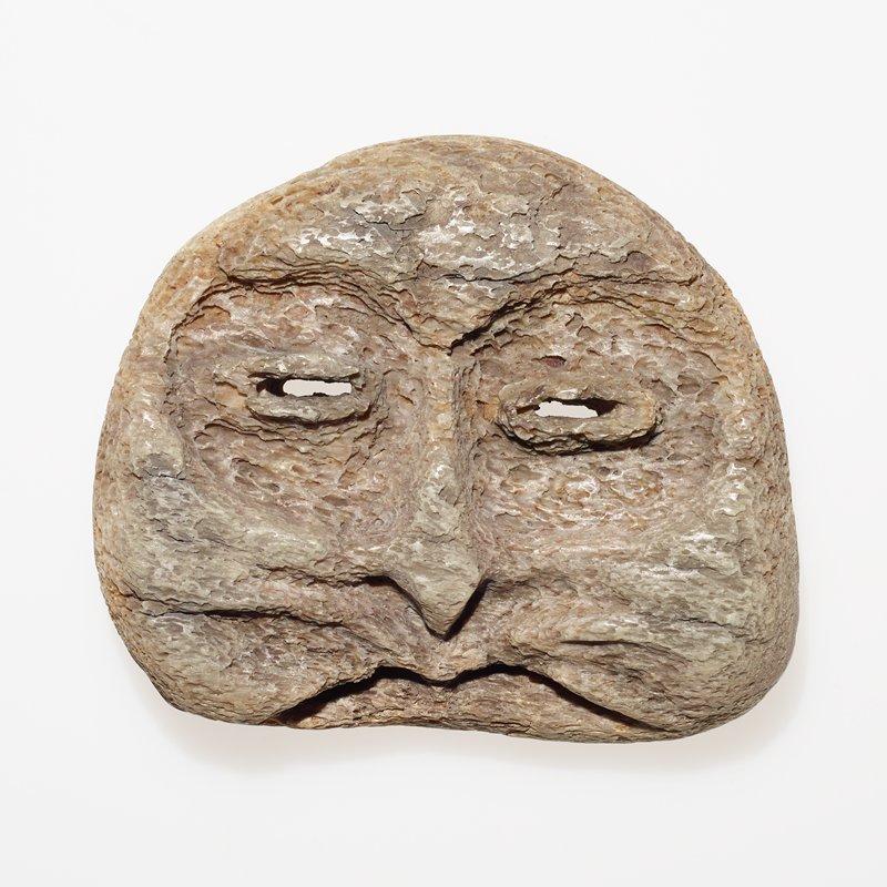 owl-like rounded face, slightly flattened at bottom; pointed flattened nose; horizontal open raised slits for eyes; two arcs make up mouth; grey/tan bone with sponge-like holes