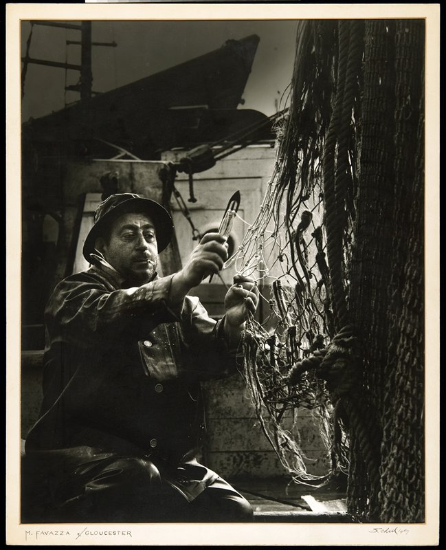 man wearing a rain hat and slicker with a cigarette in his mouth, mending a net at R; attached to mount with attached mat
