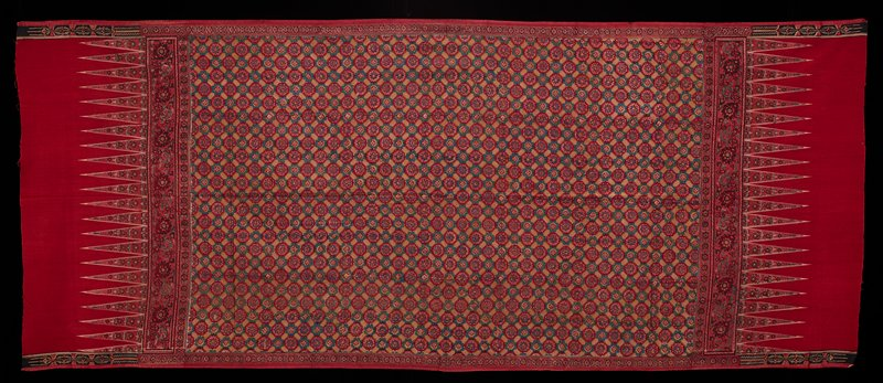 printed and resist dyed; rosettes in a diamond format with a large floral and tumpal border; maroon, pink, black, white, pale green, turquoise; borders with red flowers; zigzags at each end with red flowers and maroon sections at each end; borders on maroon sections are black, white, and maroon chased cartouches; identical to L2018.134.2