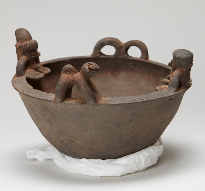 bowl with rounded bottom; decorated with a male figure wearing a hat and a female figure, both with large feet, facing each other and applied to opposite sides of rim; dog figure sideways, facing woman, and double loop applied handle opposite each other on rim; brown clay, unglazed