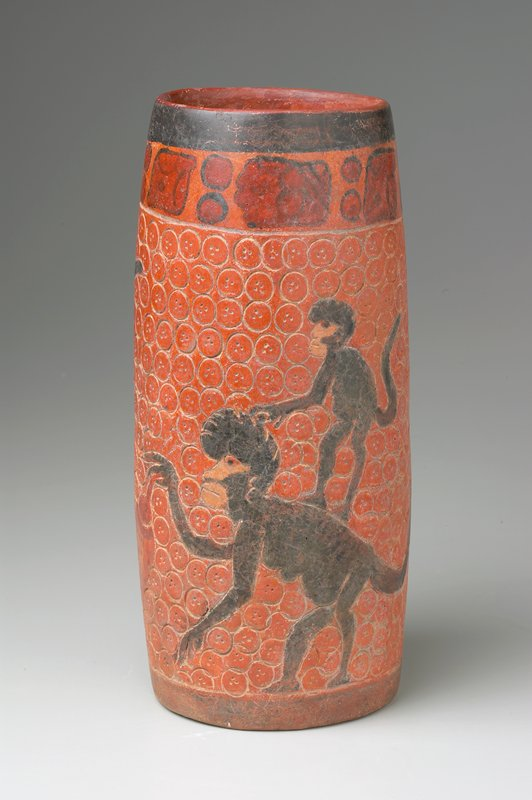 cylindrical vase, turning slightly inward at mouth; body stamped with circles containing 3 dots; 2 adult monkeys, incised and painted, each with a baby on its back; one monkey holds a large orange fruit